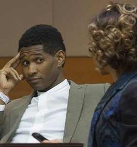 R&B singer Usher waits as he speaks with a member of his legal staff before a custody hearing at Fulton County Courthouse in Atlanta